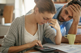 Photo of a couple looking concerned while calculating bills