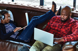 A couple on a couch with laptops