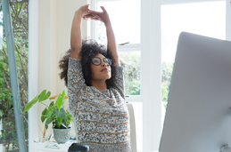 Photo of a woman stretching at her desk