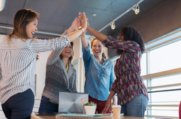 Photo of women high-fiving at work