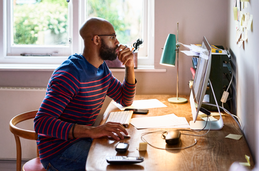 Photo of man working at his home office desk