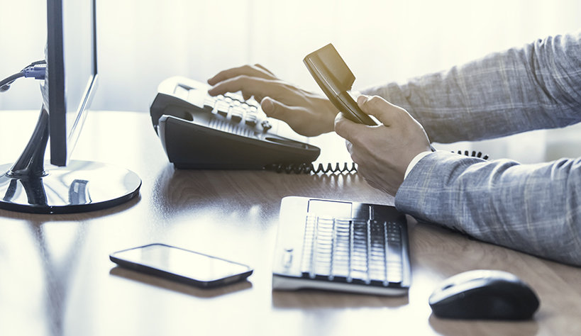Photo of a person's hands holding and dialing a desk phone