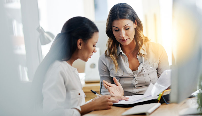 Photo of two women discussing information in a notebook