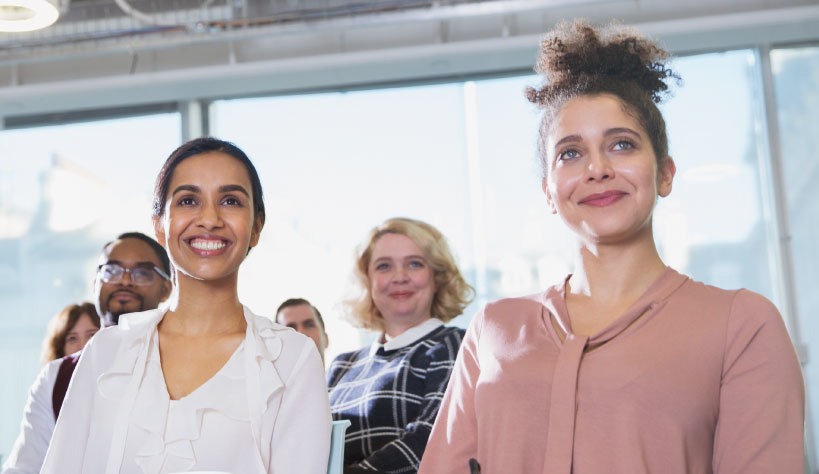 Photo of two women sitting in a presentation