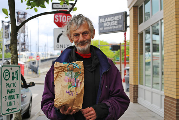 Photo of a man holding a paper bag with Hope written on it