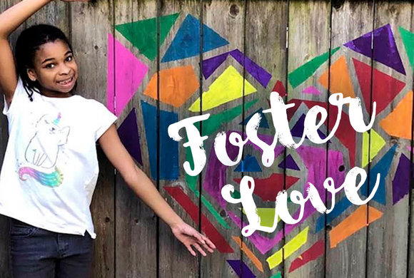 Photo of a girl at a fence painted with Foster Love