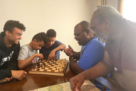 Photo of a family playing chess