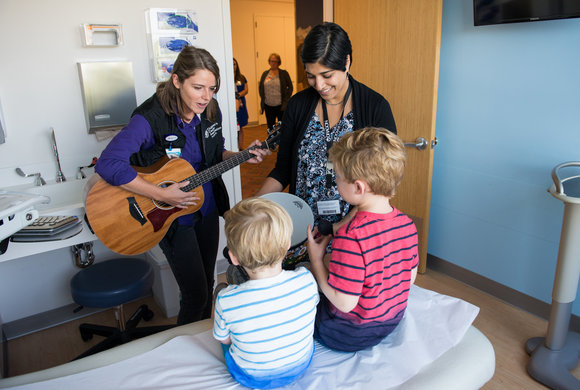 Photo of two boys listening to a woman playing guitar