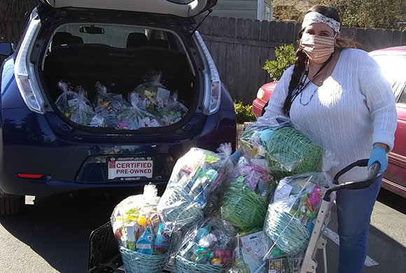 Photo of a woman loading gift baskets into a car