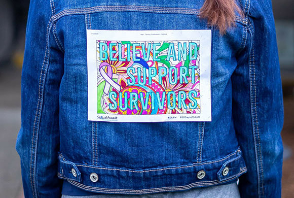 Photo of Believe and Support Survivors on the back of a jean jacket